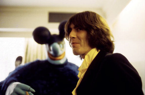 George Harrison Poses With His Yellow Submarine Cardboard Cutout Counterpart Above And Hangs A Blue Meanie Right